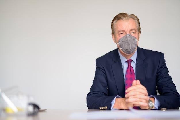 Dojrzały biznesmen myśli z maską do ochrony przed wybuchem wirusa koronowego w pracy
