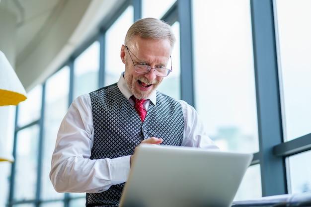 Dojrzały biznesmen, patrząc na ulepszenia czytania laptopa, siedząc w pobliżu okna w swoim biurze. panoramiczny widok na miasto w tle. zdjęcie biznesowe