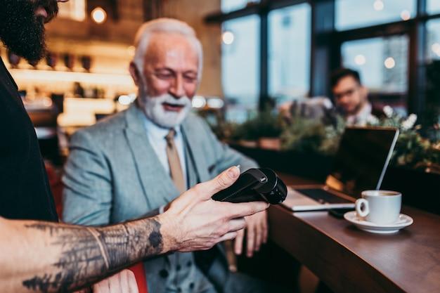 Dojrzały biznesmen płaci zbliżeniową kartą kredytową z technologią nfc.