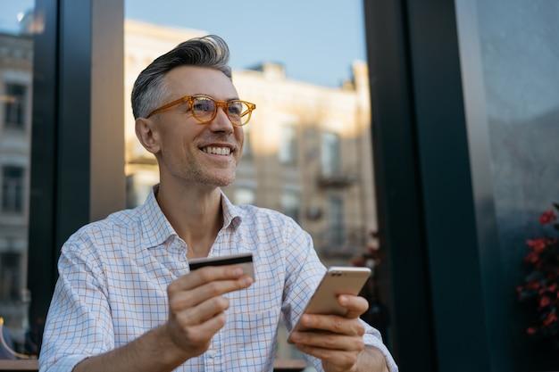 Dojrzały biznesmen posiadający kartę kredytową, zakupy online, przy płatności