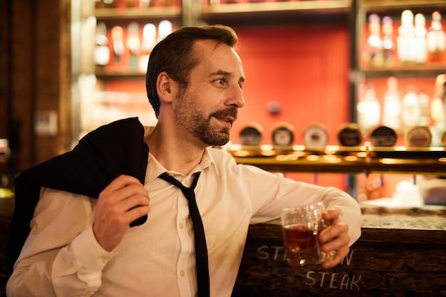 Dojrzały biznesmen relaksuje w barze