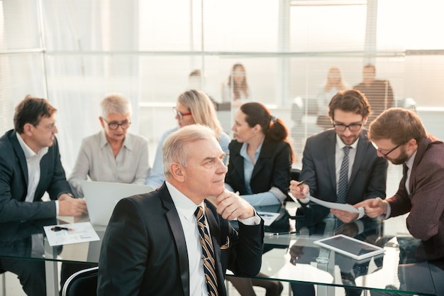 Dojrzały biznesmen siedzi przy biurku. pomysł na biznes.