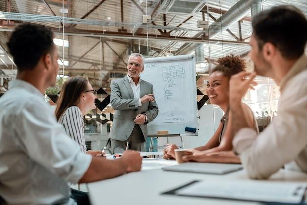 Dojrzały biznesmen stojący przy tablicy i wyjaśniający coś swoim kolegom