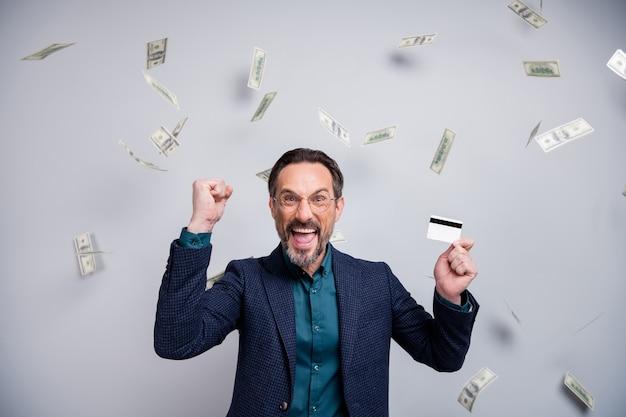 Dojrzały biznesmen trzymać kartę kredytową podnieść wygraną pięść z latającymi pieniędzmi
