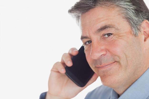 Dojrzały biznesmen używa telefon komórkowego