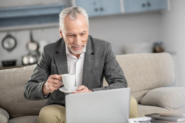 Dojrzały biznesmen. wesoły mężczyzna jest w domu i pochyla głowę, patrząc na swojego laptopa