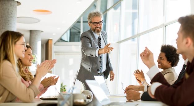 Dojrzały biznesmen wyjaśnia strategię grupie wieloetnicznych ludzi biznesu podczas pracy nad nowym projektem w biurze