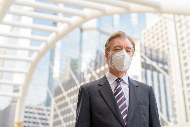 Dojrzały biznesmen z maską do ochrony przed epidemią koronawirusa na moście skywalk