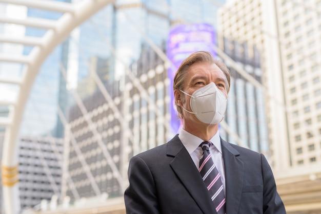 Dojrzały biznesmen z maską do ochrony przed myśleniem o epidemii koronawirusa na moście skywalk