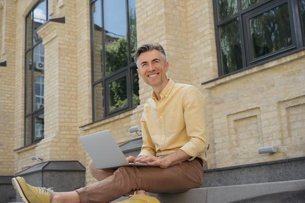 Dojrzały biznesmen za pomocą laptopa na zewnątrz. freelancer pracuje, pisze na klawiaturze