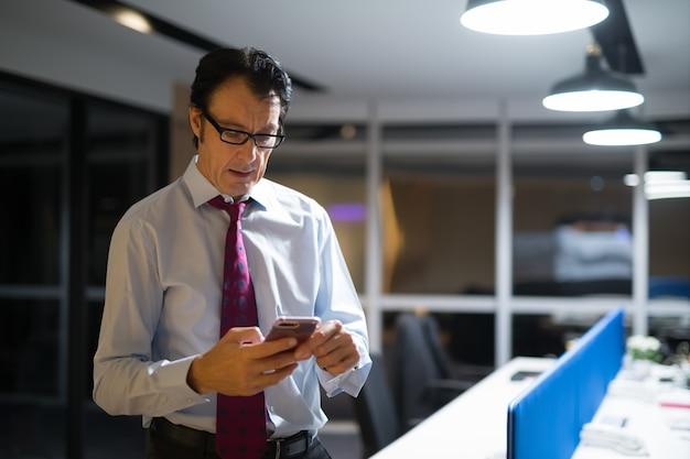 Dojrzały biznesmen za pomocą telefonu komórkowego w biurze w nocy