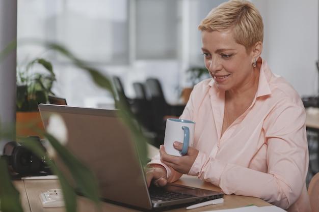 Dojrzały bizneswoman pracuje przy biurem
