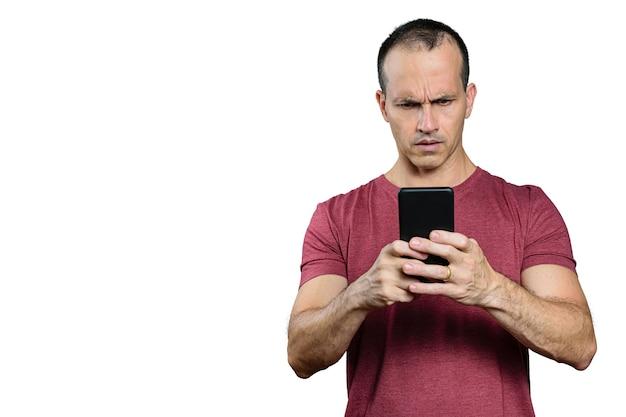 Dojrzały brazylijczyk patrzy na swojego smartfona i robi minę z dezaprobatą.