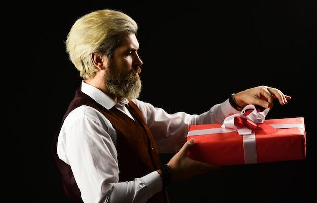 Dojrzały brodaty hipster trzyma pudełko na prezent. specjalna okazja. pudełkowy pakiet wakacyjny. dostarczanie cennego produktu. idealny prezent. zakupy online. czarny piątek. przystojny mężczyzna pudełko. ekskluzywny i niepowtarzalny.