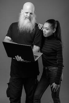 Dojrzały brodaty łysy mężczyzna i młoda piękna azjatka razem na szarej ścianie w czerni i bieli