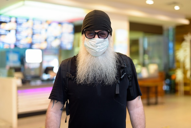 Dojrzały brodaty mężczyzna hipster jako backpacker w masce i okularach przeciwsłonecznych w centrum handlowym