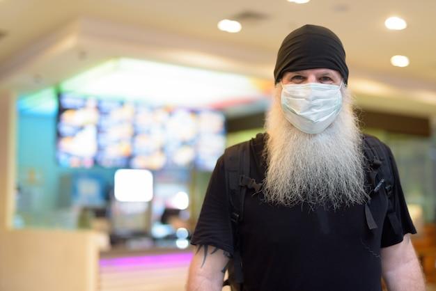 Dojrzały brodaty mężczyzna hipster jako backpacker w masce wewnątrz centrum handlowego