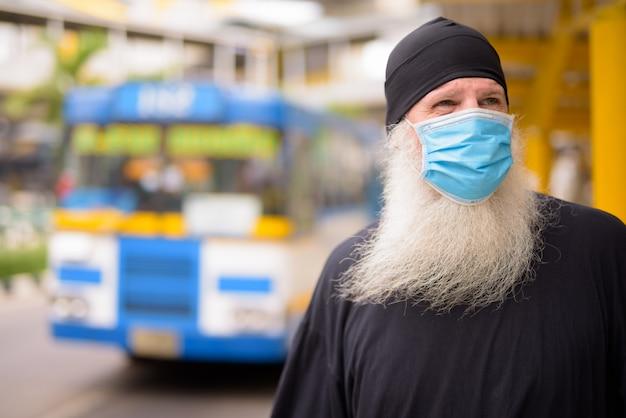 Dojrzały brodaty mężczyzna hipster z maską myśli, czekając na przystanku autobusowym