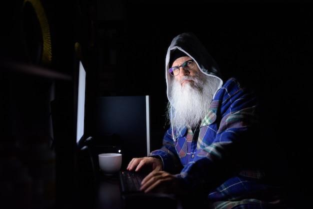Dojrzały brodaty mężczyzna hipster z okularami, pracując w godzinach nadliczbowych w domu w ciemności