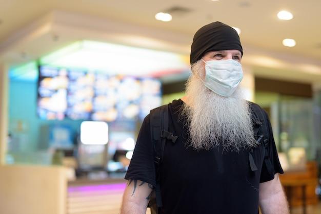 Dojrzały brodaty mężczyzna jako backpacker z maską myśli wewnątrz centrum handlowego