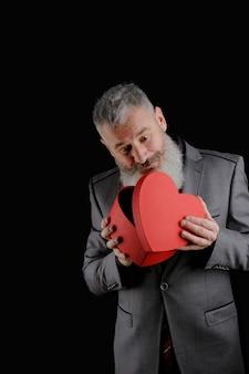 Dojrzały brodaty mężczyzna nosić szary garnitur posiada czerwone pudełko w kształcie serca, na białym tle czarne tło
