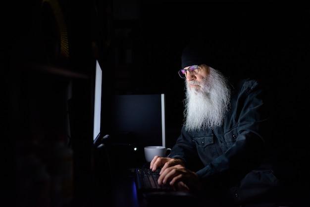 Dojrzały brodaty mężczyzna pracuje w godzinach nadliczbowych w domu późno w nocy w ciemności