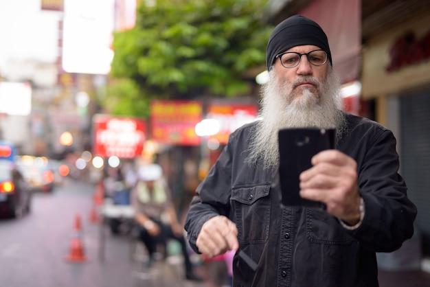 Dojrzały brodaty mężczyzna przy użyciu telefonu w chinatown