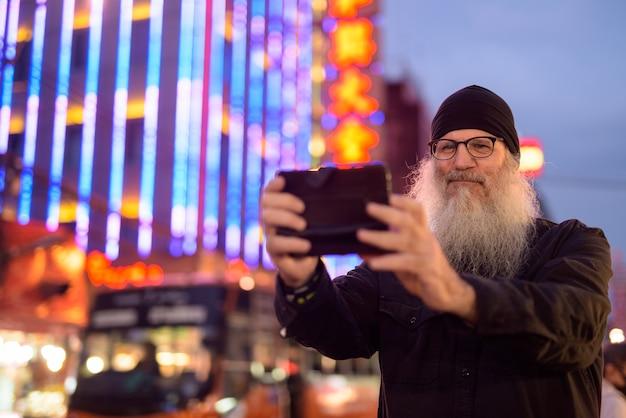 Dojrzały brodaty mężczyzna robi zdjęcie z telefonem w chinatown w nocy