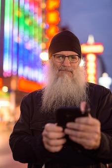 Dojrzały brodaty mężczyzna turystyczny w okularach przy użyciu telefonu w chinatown w nocy