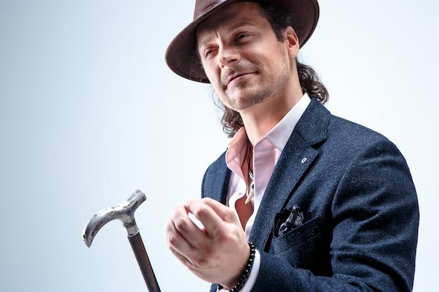 Dojrzały brodaty mężczyzna w garniturze i kapeluszu trzyma laskę. na białym tle na szarym studio.