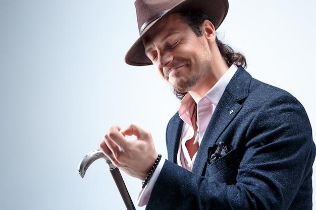 Dojrzały brodaty mężczyzna w garniturze i kapeluszu trzyma laskę. pojedynczo na szarym.
