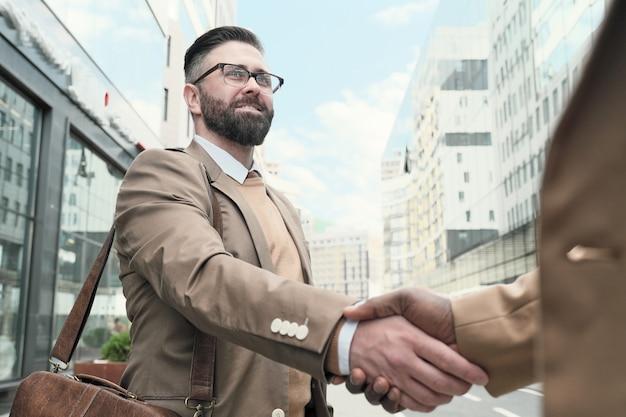 Dojrzały brodaty mężczyzna w okularach wita swojego kolegę na zewnątrz