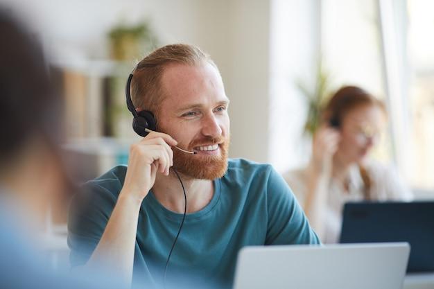Dojrzały brodaty mężczyzna w słuchawkach pracuje przy stole z laptopem w biurze