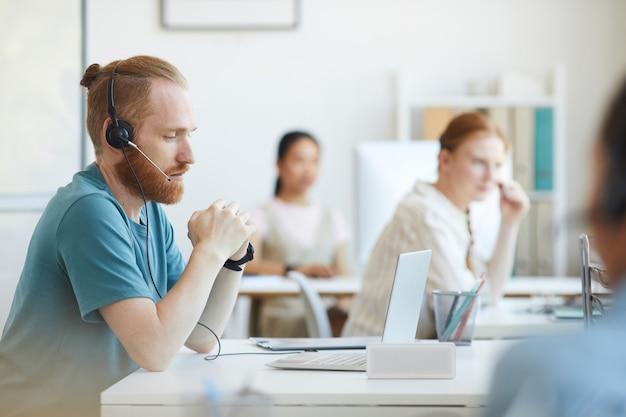 Dojrzały brodaty mężczyzna w słuchawkach siedzi przy stole przed laptopem i konsultuje się z klientem w biurze