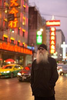 Dojrzały brodaty mężczyzna z okulary myśli w chinatown nocą