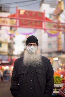 Dojrzały brodaty turysta w masce w celu ochrony przed wybuchem wirusa koronowego w chinatown