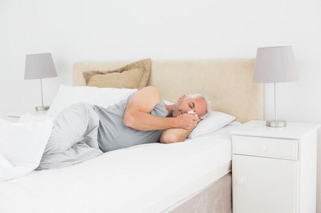 Dojrzały człowiek śpi w łóżku