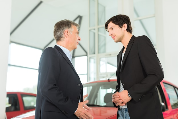 Dojrzały dealer i młody człowiek z samochodem w salonie samochodowym