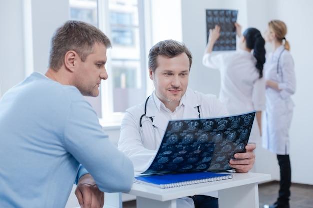 Dojrzały, doświadczony, pewny siebie terapeuta cieszy się wizytą z pacjentem i analizuje skan mr, podczas gdy pielęgniarki lubią dyskutować z tyłu
