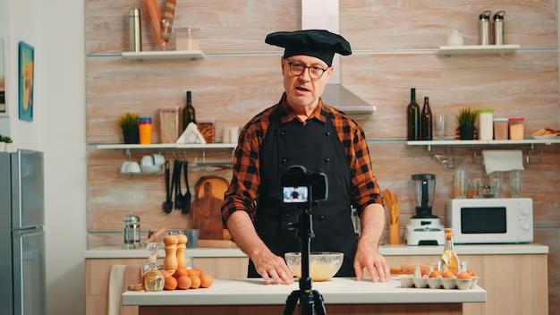Dojrzały, doświadczony piekarz wyjaśniający przepis na samouczek nagrywania publiczności w mediach społecznościowych. emerytowany bloger, wpływowy szef kuchni, korzystający z technologii internetowej, komunikujący się, strzelający za pomocą sprzętu cyfrowego