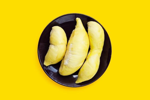 Dojrzały durian w talerzu na żółtym tle.