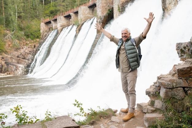 Dojrzały, ekstatyczny męski turysta z podniesionymi rękami, stojący na skale przy wodospadach i cieszący się letnią wycieczką