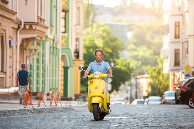 Dojrzały facet jedzie żółty skuter.