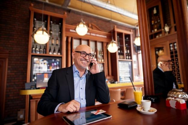 Dojrzały fachowy rozochocony biznesmen używa laptop na telefonie i podczas gdy siedzący w sklep z kawą.