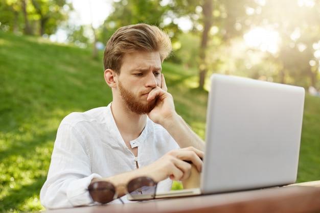 Dojrzały imbirowy przystojny mężczyzna z laptopem w parku