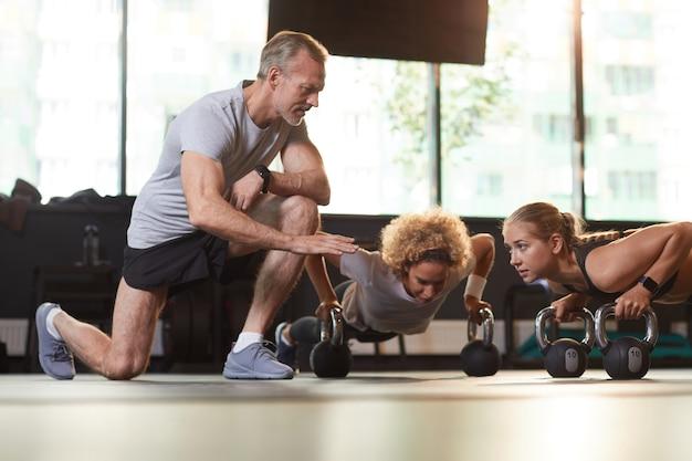 Dojrzały instruktor udzielający instrukcji młodym kobietom podczas ćwiczeń z hantlami na siłowni