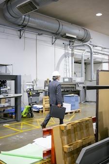 Dojrzały inżynier w oficjalnym garniturze i kasku, chodzący po hali produkcyjnej, z walizką z narzędziami