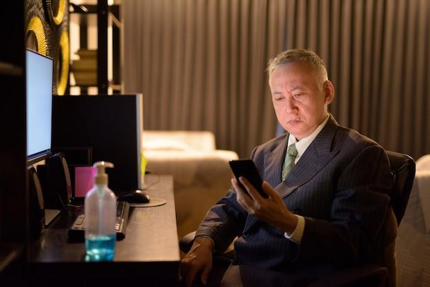 Dojrzały japoński biznesmen używa telefon podczas gdy pracujący nadgodziny w domu póżno przy nocą