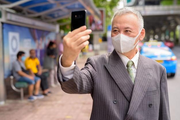 Dojrzały japoński biznesmen z maską bierze selfie przy przystankiem autobusowym