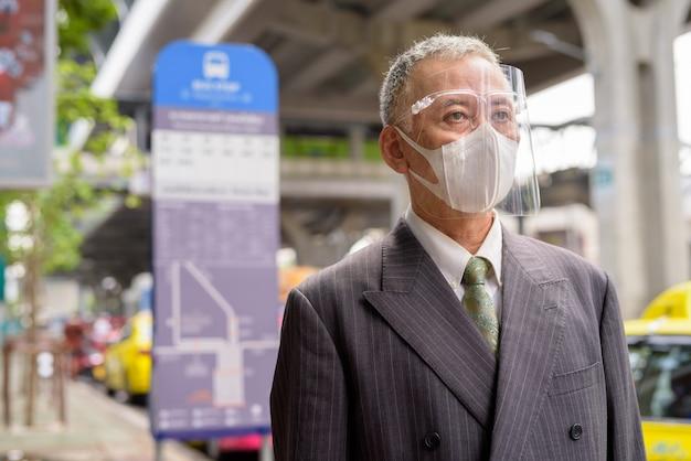 Dojrzały japoński biznesmen z maską i osłoną twarzy czeka przy przystankiem autobusowym